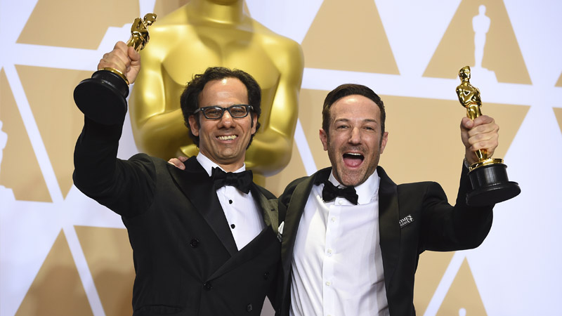 Dan Cogan and Bryan Fogel, winners of the award for Best Documentary Feature for 'Icarus,' pose in the press room at the Oscars.